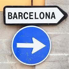 "A street sign reading ""Barcelona"" over a blue direction arrow"