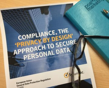 A pair of glasses and notebook on a Symantec Compliance guide
