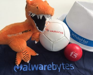 A plush T-Rex next to a ball and a hat