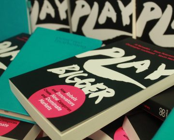 A Play Bigger book and a Positive branded notebook on the Play Bigger stand
