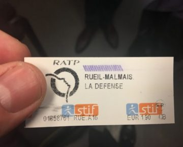 A hand holding a French public transport ticket